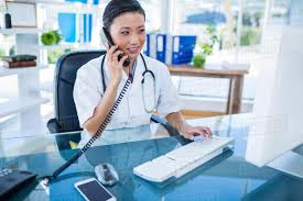 Doctor Having Phone Call And Using Her Computer In Medical Office