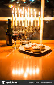 celebrating hanukkah with menorah candlestick with 8 candles by the window with the night city view stock image
