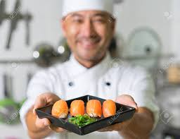 Sushi Cook Smiling Asian Chef With Sushi Focus On Sushi