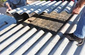 two roofing contractors carrying a corrugated metal sheet for roof replacement