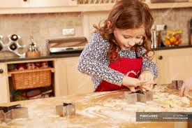 Girl Baking Star Shape Pastry At Kitchen Table Brown Hair One
