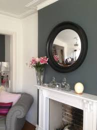large cavetto convex mirror in waxed black finish hanging above a fireplace image