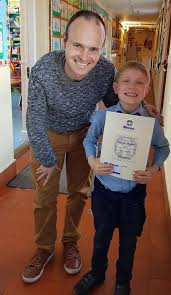 hayden higgins loves going to at scoil naoim lorcain and he is pictured with his teacher