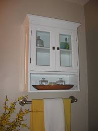 white wooden mounting bathroom cabinet with double glass doors and lower open shelf also chrome towel