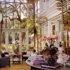 tropical living rooms: tropical living room with high ceiling french doors conservatory brick floors golden