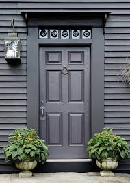 a six panel door on a colonial era house is topped with a transom