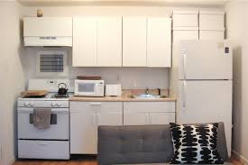 white refrigerator in kitchen. white boxes for storage above the fridge are nearly camouflaged in this all-white kitchen → laura\u0027s living better with less on apartment therapy refrigerator