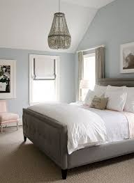 Blue gray bedroom with beaded chandelier and gray bed