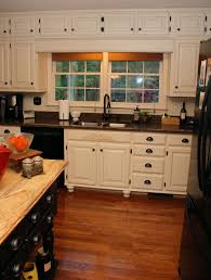 kitchen white wooden kitchen cabinet and black granite countertops on brown wooden floor connected by