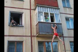 guys in red boxers hanging from a balcony while a woman screams and a man  points a gun at them