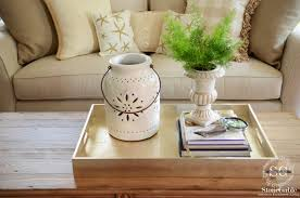 the fern is tall the pottery is medium height the books are low and the sides of the tray are even lower this let s our eyes move around the tray and
