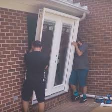 two men tilting a patio door into place