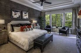 master bedroom with dark accent wall and tray ceiling