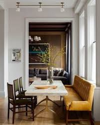 kevin dumais tribeca mid century apartment dmodern dining room wood floors yellow seating with green chairs marble table with metal base neutral palatte