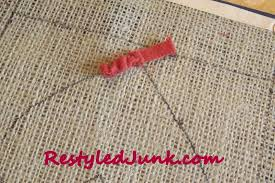 following the traced line insert the hook in a hole beside the first grab the strip on the back of the rug and pull the loop through to the front until