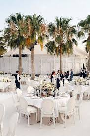 wedding reception decorations big palm trees white round tables yellow and pink roses bouquets wedding ceremony