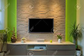 modern living room interior tv mounted on brick wall with black screen and ambient light