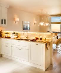 Cocina Abierta Al Office Con Muebles En Blanco Y Luces Encendidas. Una  Iluminación Más Sostenible