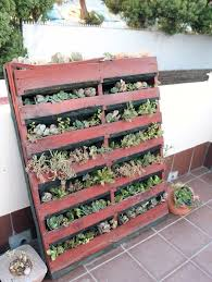 A vertical pallet planter propped against a wall