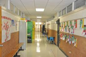 hallway at school. as you look right down this hall with no storage in classrooms shelves line the hallway at school h