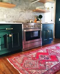 green kitchen cabinets marble backsplash oriental rug and floating shelves comprise this kitchen