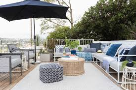 the living area of emily henderson s newly transformed deck featuring an indoor outdoor rug