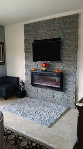 how to add decorative stone wall panels around a mounted tv and fireplace
