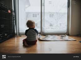 looking out door. Baby Sitting On Floor Looking Out Glass Door M