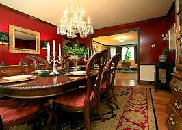 small classic dining room with red wall color schemes and extra large rugs under oval wood table also using square wall mirror