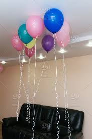 multi colored balloons with helium under the ceiling in the living room with black leather sofa decoration