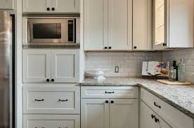 inside corner of kitchen has painted white cabinets in a shaker style with oiled brass pulls