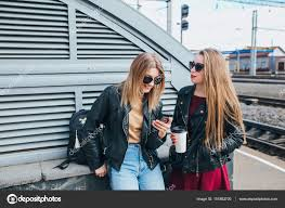 outdoor lifestyle portrait of two best friends hipster girls wearing stylish leather jacket