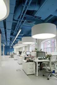 the saturated blue ceiling and wall surrounds bright whites in this media agencys office architectural design office