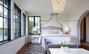 relax in this lovely master bedroom featuring a wall lined with windows fitted with black moldings and dressed in white and taupe curtains facing an iron