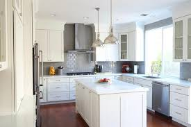 industrial luxe kitchen design features white shaker cabinets white glass subway tile backsplash stainless