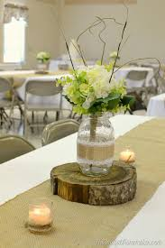 mason jar centerpiece on top of wood slice on top of burlap runner for  wedding