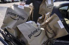 amazon prime now bags full of groceries are loaded for delivery by a part time