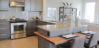 the kitchen features a breakfast bar stainless steel appliances and plenty of counter space all in a open concept design with the great room