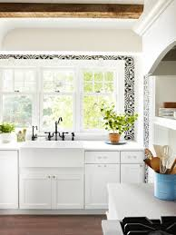 small white kitchen with wood beams and patterned tile