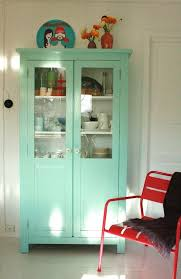 19 Neutral interior with a mint cupboard and a statement red chair