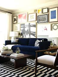 royal blue living room furniture gallery wall dark blue velvet sofa black and white stripe rug and a live edge coffee table living rooms love the grey walls