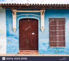 Wooden door designing Modern Front Of An Old House Brown Wooden Door With White Designing Over It And Small Window Beside It With Iron Grill Old Vintage Colonial House Architect Alamy Front Of An Old House Brown Wooden Door With White Designing Over