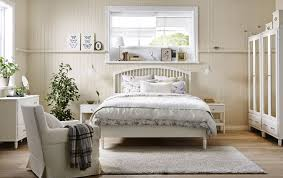 A bedroom in country style with a large bed, two bedside tables, chest of