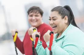 hispanic woman friend exercising with resistance bands