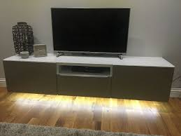 wall hung ikea besta white tv unit with beige doors glass top led tape light fitted underneath