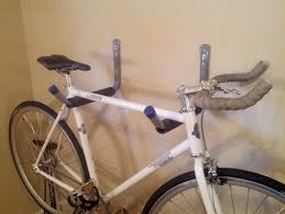 Cheap and simple DIY bike rack. All you need is two wall book hooks from  home depot at 7 bucks a piece ...