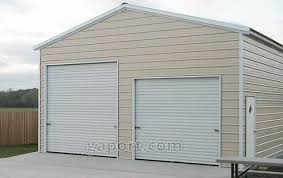tan garage with concrete slab base and two roll up garage doors on the end