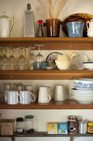 open storage shelves in a farmhouse kitchen with assorted kitchenware and ings mounted onto the wall
