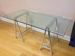 a nice glass top table or desk with saw horse aluminum legs they are high