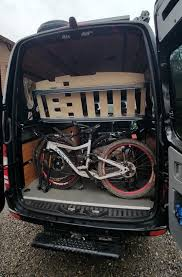 sprinter van with bikes shown with adjustable bed tilted up for access